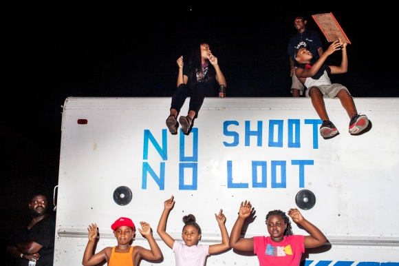 August 19th, 2014. Ferguson, MO. Children dance to music playing from a truck with the words ?no shoot, no loot? written on it and parked in a lot on West Florissant Ave. during a protest on Aug. 19, 2014, in Ferguson, Mo. Moments later riot police insisted that the protesters keep marching in circles around the designated protest area and not stop to dance.