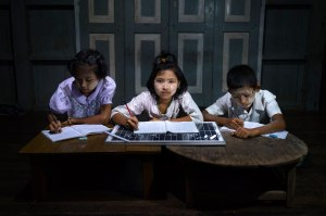Grade 11 students do their homework in a solar-powered after-school community center near in Taman Chan Village, in Dala Township.